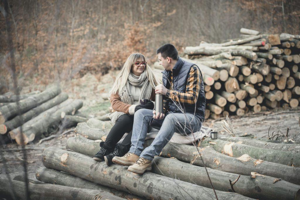 Para narzeczonych pijących herbatę na drewnie o wschodzie słońca